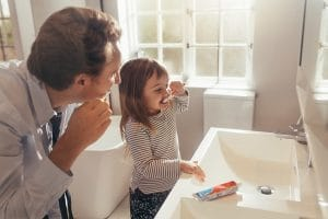 young girls brushes her teeth with her father in the morning