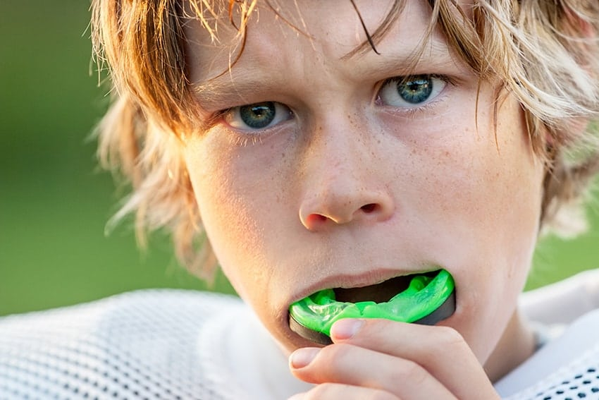 A young football playing putting a mouthguard in, ready for the game! These professional mouth guards not only protect your teeth, they can improve your performance.