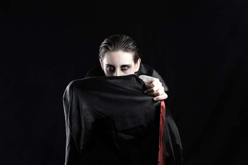 A vampire hiding their face to cover up a bite. You no longer have to be Count Dracula to have fangs