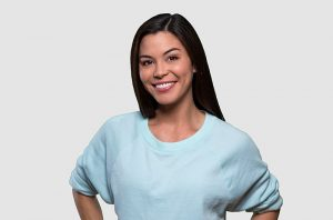 A pretty woman in a white sweatshirt has a smile that shines due to general dentistry