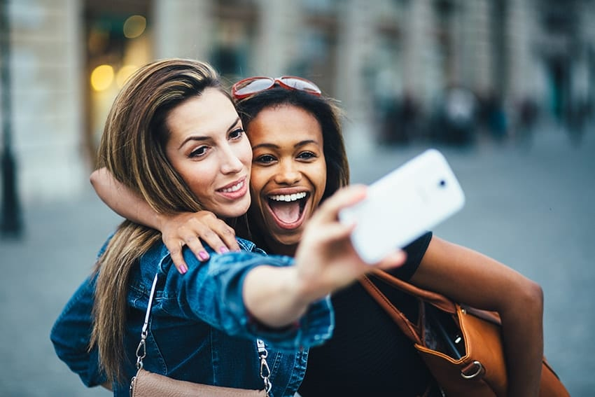 Two friends enjoy a laugh while taking a selfie. Social media is great, but with changes to Instagram, you may now have to show off your true smile?