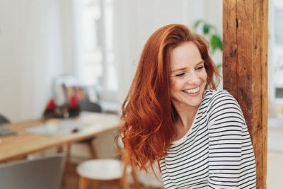 beautiful red haired woman laughing in her studio at home