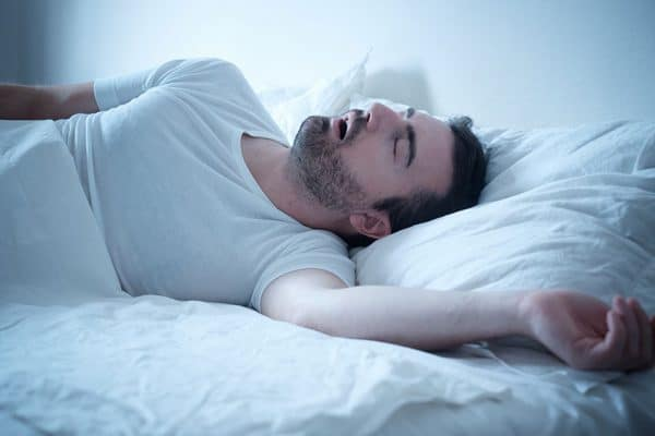man sleeping in bed snores loudly with mouth wide open